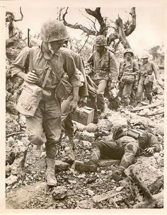 U.S.Soldiers Pass Dead Enemy Soldier. Pacific Theater.