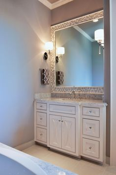 A beautiful white vanity adds elegance and brightness to this lovely gray bathroom. Gray and white mosaic tile frames the mirror above the vanity, tying the room's color scheme together.