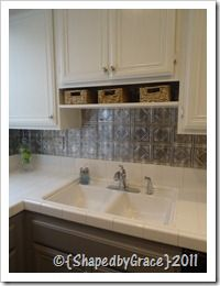 Easy DIY Backsplash using Home Depots adhesive stainless steel look tile sheets. At 20 bucks a sheet it was still cheaper than tile & grout. It goes on with either adhesive glue OR double sided industrial tape. {Which is what she used.}