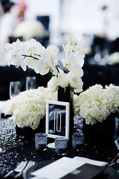 Even table numbers match the modern black and white theme ~ https://www.insideweddings.com/weddings/black-and-white-modern-wedding-with-unique-details-in-cincinnati/698/