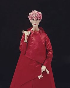 Mary Jane Russell  wearing red satin evening coat with Kabuki-like folds, with a jeweled chrysanthemum hat. Coat by Arnold Scaasi - Vogue December 1955 © Richard Rutledge