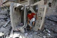 A Palestinian boy looks through the remains of a car hit by an Israeli air strike in Gaza city.