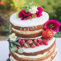 A rustic summer two tier naked cake. Madeira sponge layered with homemade gooseberry jam, gooseberry curd and mascapone cream. Decorated with bright summer flowers, strawberries and raspberries. Photo by Lauren by the Sea.