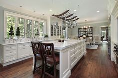 White kitchen with white walls and island with dark wood floors. Stainless steel pot rack above island.