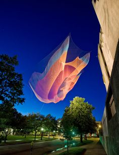 "Janet Echelman's 230-foot-long aerial sculpture ""1.26"" suspends from the roof of the 7-story Denver Art Museum above downtown street traffic to commemorate the inaugural Biennial of the Americas."