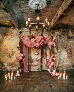 For a rustic Indoor wedding ceremony - a backdrop with cascading blush pink fabric and flowers