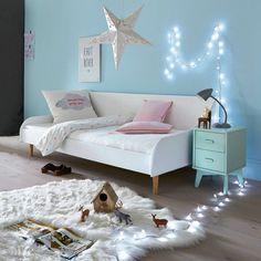 Une chambre de petite fille bleu turquoise avec une guirlande lumineuse et une suspension étoile en fer forgé blanc. Cette chambre de petite fille avec table de chevet bleue vert est moderne et change des stéréotypes de petites filles.