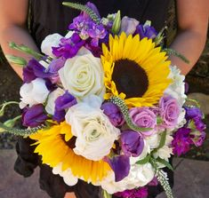 White purple and yellow bridal bouquet in sunflowers, tulips, stock, hydrangea, roses, ranunculus, veronica, lizzy. Designed by Nina with By Request. www.byrequest.us