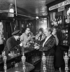 Ministry of Information Photo Division Photographer -- Mrs Pitt, wife of the landlord, pours a pint of beer for a naval officer in the saloon bar of 'The Cricketers' pub in Brighton during -- High quality art prints, canvases -- Imperial War Museum Prints London Pubs, Old London, Old Pictures, Old Photos, International Beer Day, Monocycle, Pub Interior, Pint Of Beer, Old Pub