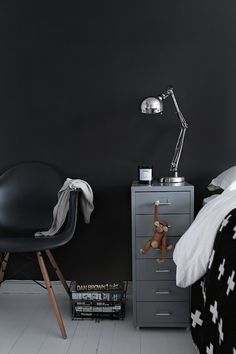 Black and white boy's bedroom with black paint color, black Eames Molded Plastic Dowel-Leg Armchair, white washed plank floors and Ikea Helmer Drawer Unit on Casters - Silver.