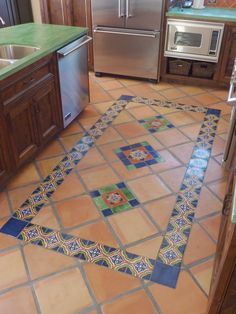 Kitchen remodel using Mexican tiles on floor by kristiblackdesigns.com
