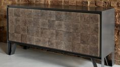 The metal sideboard is composed of panels cut from the end grain of an oak log.