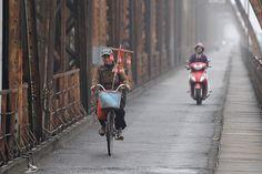 A woman selling salt is riding on Long Bien bridge