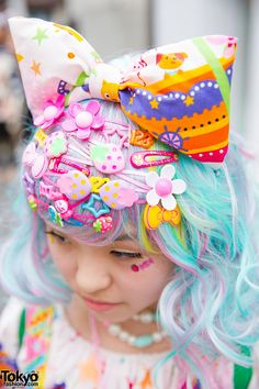 This blue-and-pink-haired girl is Nodoka. She's wearing colorful Japanese decora fashion – including an oversized bow as well as several decora hair pins on her bangs. Nodoka made her carousel print dress and bag herself, and paired them with Roni sneakers that feature platforms and pink ribbon laces. Her necklaces, rings, accessories and ribbon are from 6%DokiDoki, and her watches are from Mikazuki Momoko. She's also wearing a panda backpack and knee high socks. (Tokyo Fashion, 2014)