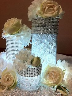 DIY centerpieces. 1)glass jars 2)diamond sheet stickers 3) fish bowl rocks 4) fake white roses 5) LED tealights to hide in center