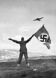 A German pilot waves down a fellow Luftwaffe airplane for extraction following his own plane being shot down. 1940.