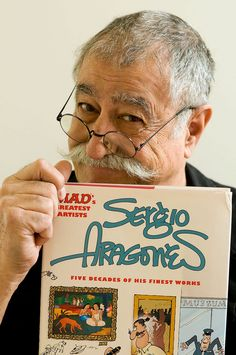Sergio Aragones holding up a book collection of some of his work.
