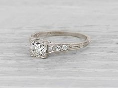 Late Edwardian vintage engagement ring made in platinum set with an EGL certified approximately .65 carat I-J color VS2 clarity old European cut diamond and accented by six single cut diamonds. Circa