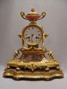 Francés de porcelana antigua rosa y reloj de bronce de la chimenea.