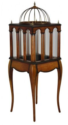 MAHOGANY DOMED BIRD CAGE ON STAND 20th Century Stained wood birdcage with glass arcade and iron dome sits atop a scalloped apron and tapered legs.