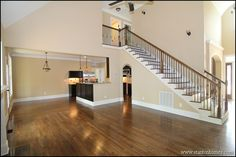 An arched hallway runs underneath this hardwood staircase, connecting the great room and formal dining.