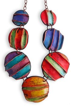 Exposed polymer, With a wink at fashion, the raised exposed seams on Anarina Anar's latest polymer disk necklace mirror a trend in clothing finishes.  Tiny flecks of color on all the stripes unify Anarina's bright colors. The seams are accented with contrasting colors. Is it fabric? Is it ceramic?  This Greek artist's secret ways with alcohol inks give her polymer more vivid, transparent, liquid colors than tinted clays might allow