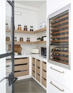 Beautiful kitchen pantry with built-in wine fridge, open shelving, and mixed finishes. Wood drawer fronts and white cabinetry