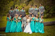 Think I'm going with gray tuxedos and turquoise dresses. Looks good together. Flowers possibly yellow with a little orange added