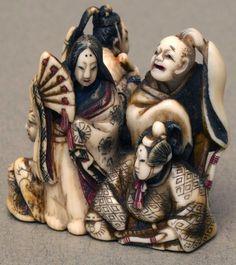 Netsuke Ivory with oloured detail. 5 mandarians accompanied by a geisha girl holding fan.