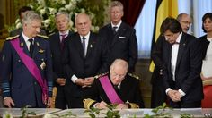 King Albert II signed the abdication documents watched by Philippe (L) and Prime Minister Elio Di Rupo (R)