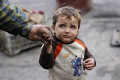 A child reacts as he holds his father's hand after hearing shelling in Aleppo on Nov. 29. By Molhem Barakat.