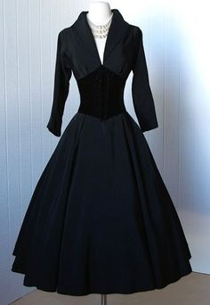 1950's cocktail party dress made of gorgeous black faille and jet black velvet.  Designed in the classic New Look silhouette with a dramatic portrait style collar, plunging pleated neckline, a deep corset laced velvet waist, and a full and swingy skirt with an attached underskirt.  By Suzy Perette.