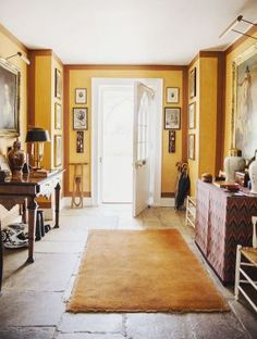 Sunny yellow, stone floor, art and accessories.....right out of the English countryside (India Hicks)