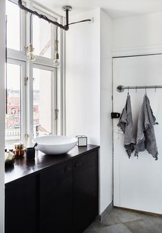 Simple and nordic bathroom featuring furniture from Ikea and pendants from Normann Copenhagen.