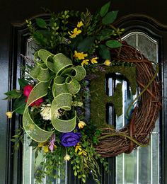 Beautiful Grapevine Wreath with moss covered monogram. This wreath is accented with silk florals in yellow, purple hot pink and white and a