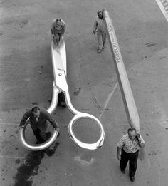 Movie stagehands pushing a pair of gigantic scissors on a dollie next to two men carrying a pencil for 'The Incredible Shrinking Man', Universal Studios. Photograph by Allan Grant, September Hollywood, California. Via the Life photo archive. Photo Vintage, Vintage Photos, Fred Herzog, Herbert List, Mary Ellen Mark, Karl Blossfeldt, Edward Steichen, Cinema Tv, Kino Film