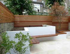 Horizontal wood fence, white concrete planters, wall-mounted floating wood benches.