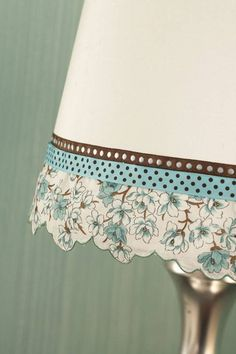 To soften a drum shade, cut the scalloped edge from a hankieand attach it using fabrics glue; glue grosgrain ribbons on top.