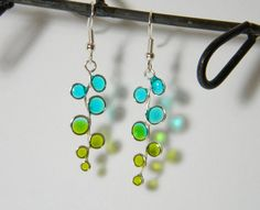 blue and green colored stained glass geometric bubble resin earrings  These delicate ice resin earrings display a beautiful union of sky blue and olive green. The color combination reminds me of spring flowers with pale green leaves. The transparent bubbles glow and shine when they catch the light. These earrings would be perfect for a day out on the town or a sun filled picnic in the park. They would look lovely on your bridesmaids during a warm spring outdoor wedding.  I use dark silver…