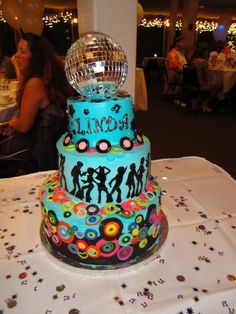 2 tier cake covered in buttercream with fondant accents. Topped with a mirrored disco ball! 50th Birthday, 70's DISCO PARTY