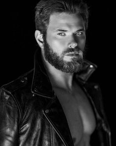 Kellan Lutz with a thick beard wearing a leather jacket.