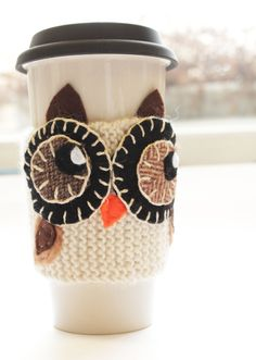 Owl cup cozy This seems like it would be pretty easy to do this yourself! Just knit the main white strip and then knit the other parts, or make them out of felt with embroidery floss, and then sow them on.