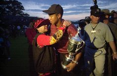 Tiger Woods holds his trophy and embraces his mother, Kultida Woods, after winning the U.S. Open at the Black Course of Bethpage State Park in 2002.