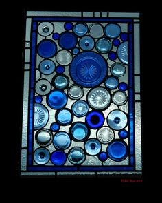 """Recycled stained glass window using blue """"depression"""" glass plates, bottles, and cups."""