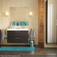 Türkis wirkt frisch und steril. Es eignet sich daher wunderbar für die farbliche Gestaltung in einem Badezimmer. Die dunkle Badezimmereinrichtung, wie der Waschtisch und der Spiegelschrank, werden durch das frische Türkis optisch aufgelockert und schaffen mit den hellen Wandfliesen ein sauberes Ambiente im Badezimmer.