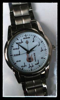7c5c2ad00799 Reloj de pulso con extensible metálico con valor de notas musicales y  guitarra al centro.