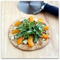 A recipe for mini pizzas with fresh apricots, crumbled goat cheese, carmelized onions and arugula.