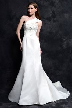 STYLE: GL044          This elegant one-shoulder gown is made in Royal Duchess Satin with a bodice that has been fully embroidered and crystallized with beading. The natural waist has been accented with a gathered band and leads to a mermaid skirt made with a chapel length train. Available in in White or Ivory.