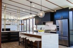 Knocking down walls made room to give the kitchen the sleek, open layout it deserved. The new flow of natural light throughout the space allowed Joanna to make a bold choice of black cabinetry with brass hardware. A marble backsplash, countertops and and a waterfall edge island keep things nice and bright.