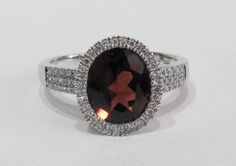 White gold ring with diamonds and a garnet. You can find it at Keswick Jewelers in Arlington Heights, IL 60005